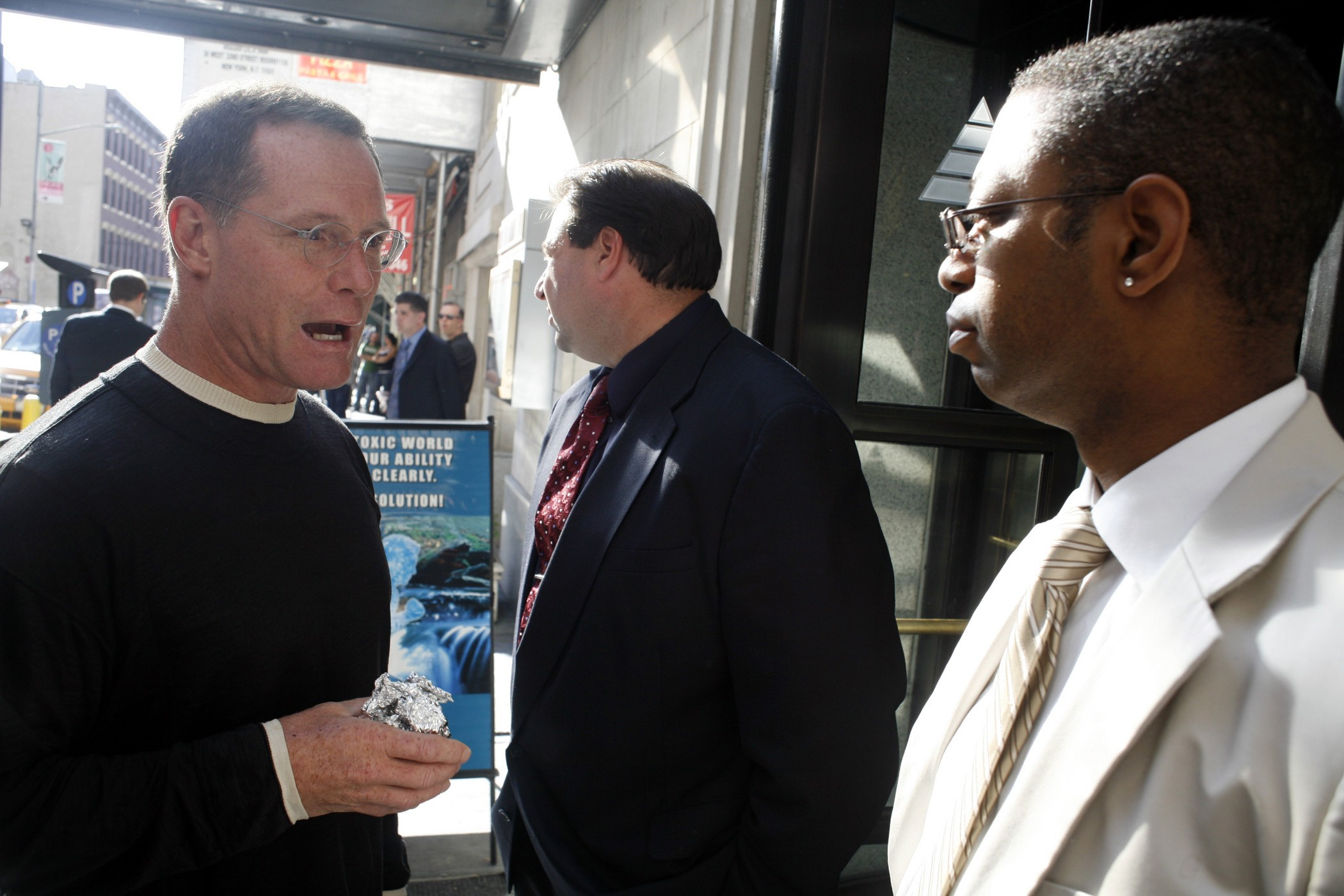 Jason Beghe explains to Scientology's hired muscle that the $1 million he paid the organization entitled him to come in. But they disagreed. Perhaps Beghe should have offered the cake in foil wrap that Anonymous had given him.More photos from the protest here.