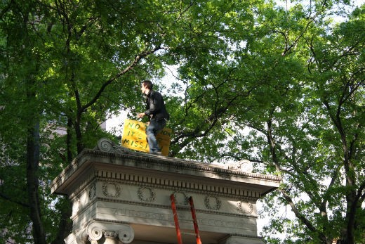 This is a guy dancing on top of the monument in front of Cooper Union. We have no idea how the hell he got up there.