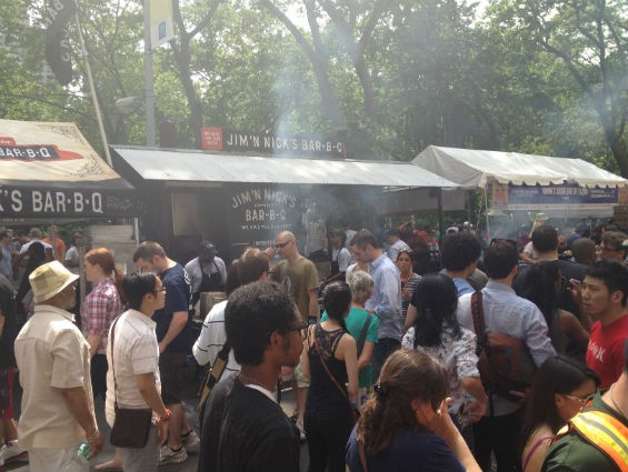 Crowds and lines under a cloud of barbecue smoke.