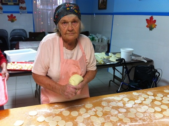 A church parishioner happily making dumplings one by one.