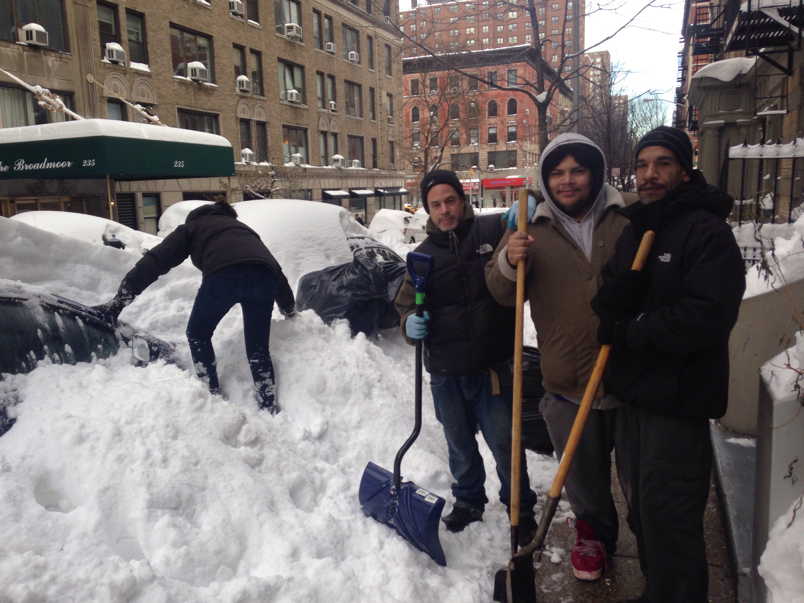 Nelson Santiago, center, stands with two of his crew members about to help an Upper West Side resident unbury her car.