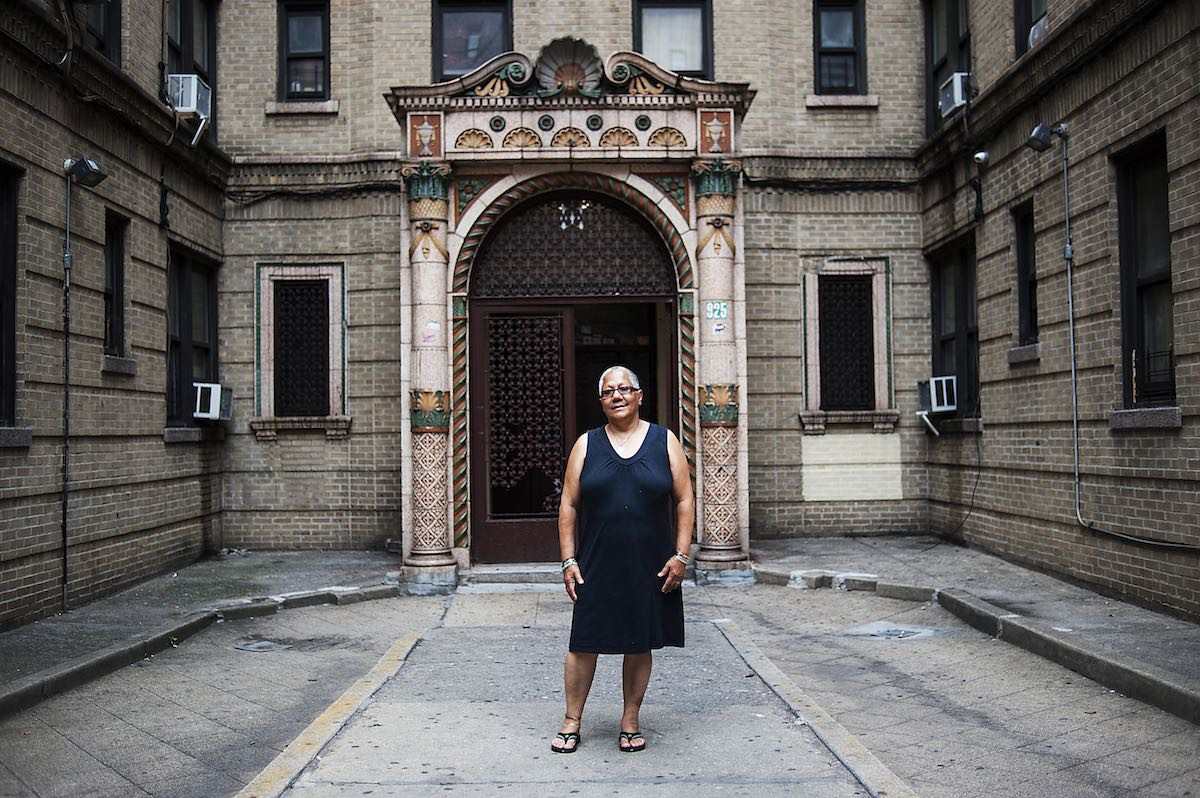 Marta Melendez stands in front of her building at 825 Gerard, which used to be surrounded by flower boxes. The landlord filled them in with concrete.