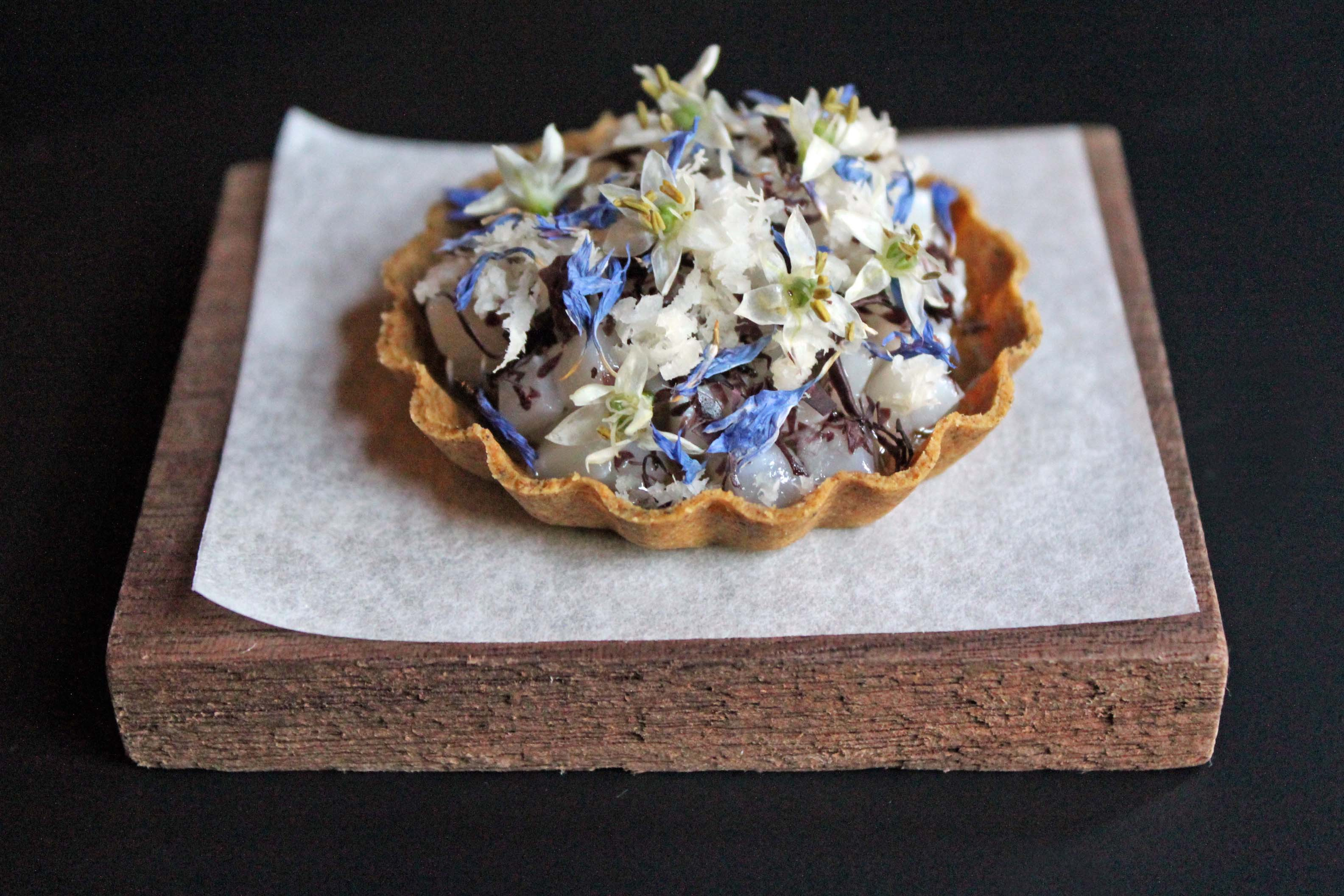 Seaweed and charred squid tart, with edible flowers