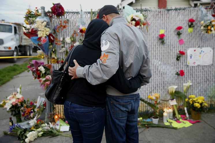 Mourners hug next to flowers near the site of the warehouse fire in Oakland, CA December 4, 2016.